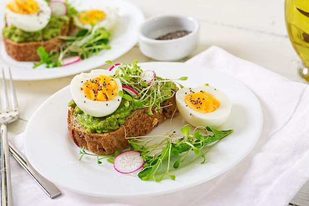 Cibo salutare. prima colazione. panino dell'uovo di avocado con pane integrale su superficie di legno bianca.