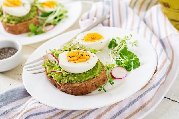 Cibo salutare. prima colazione. panino dell'uovo di avocado con pane integrale sulla tavola di legno bianca.
