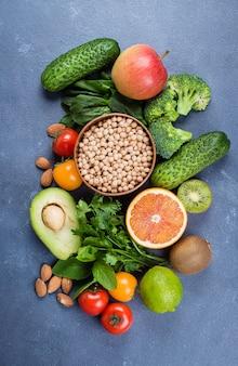 Cibo sano pulito frutta cruda, verdure, noci, cereali su sfondo di tavolo in pietra concreta