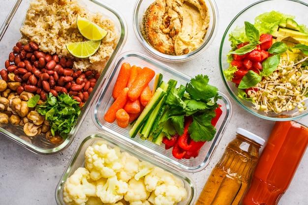 Cibo sano vegano in contenitori di vetro, vista dall'alto. riso, fagioli, verdure, hummus e succo.