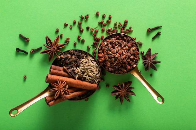 Cibo spezie concetto cinese biologico cinque spezie, bastoncini di cannella, anice stellato, semi di finocchio, pepe in grani di sichuan e chiodi di garofano in una tazza di rame