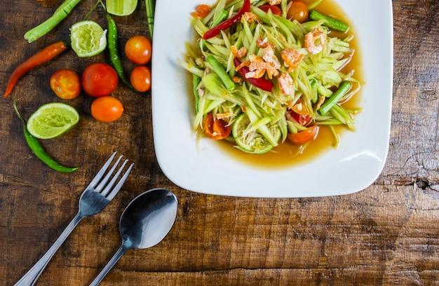 Cibo tailandese, insalata di papaya e pomodori, peperoni e condimenti su un tavolo di legno