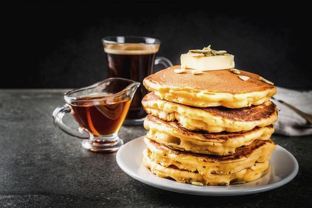 Cibo tradizionale autunnale. pila di pancake di zucca con burro, semi di zucca e sciroppo d'acero. con una tazza di caffè su un tavolo di pietra nera. copyspace