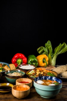 Cibo tradizionale tailandese con i peperoni dolci e bokchoy sopra la tavola contro fondo nero