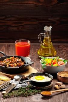 Cibo vegetariano. funghi fritti e uovo in padella di ghisa. ingredienti per la colazione rustica sul tavolo di legno.