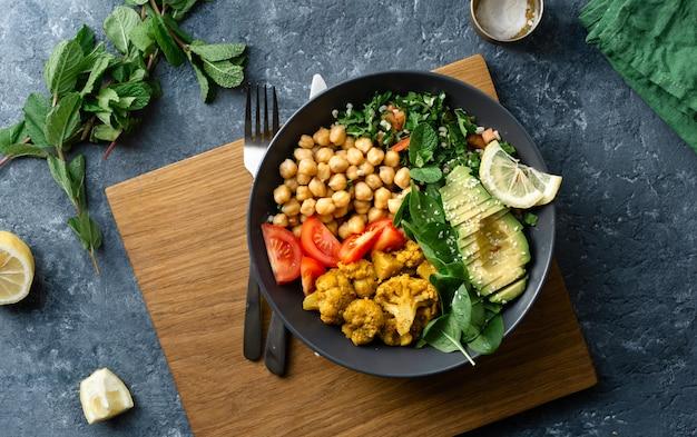 Cibo vegetariano sano con ceci, pomodoro, avocado e spinaci