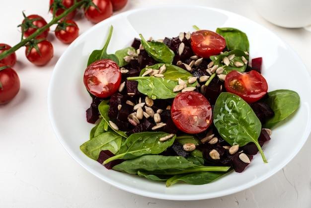 Cibo vegetariano sano. insalata con barbabietola rossa, spinaci, pomodorini e semi.