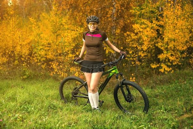 Ciclismo della donna nella foresta gialla di autunno su un prato