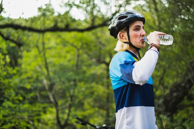 Ciclista acqua potabile da una bottiglia