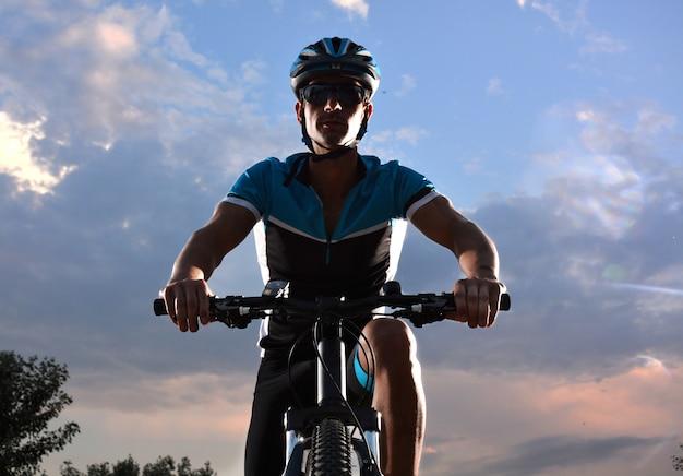 Ciclista andando in mountain bike lungo una strada solitaria