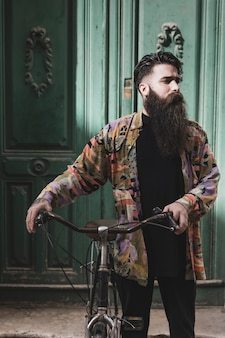 Ciclista barbuto che sta davanti alla porta di legno verde antica