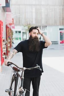 Ciclista che cammina con la bicicletta sulla strada della città