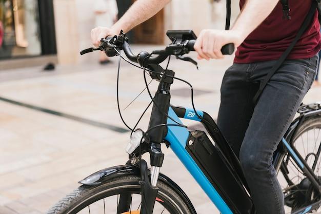 Ciclista che guida l'e-bike attraverso la città