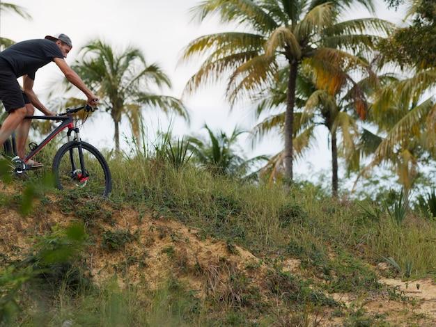 Ciclista che guida la bici sul sentiero di montagna foresta tropicale.