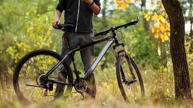 Ciclista del tipo nella foresta di autunno ad ottobre. stile di vita attivo. attività all'aperto e ciclismo