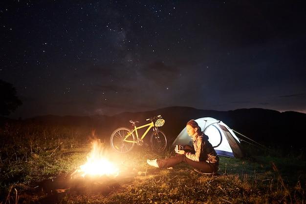 Ciclista della donna di notte in campeggio vicino al fuoco che brucia