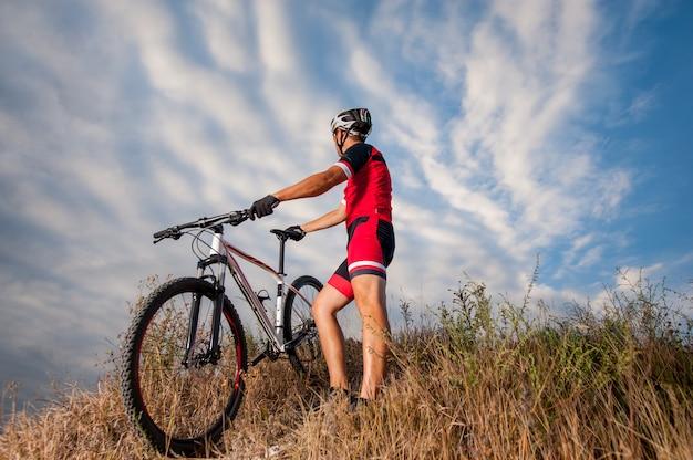 Ciclista di montagna che riposa con la sua bici contro il cielo blu