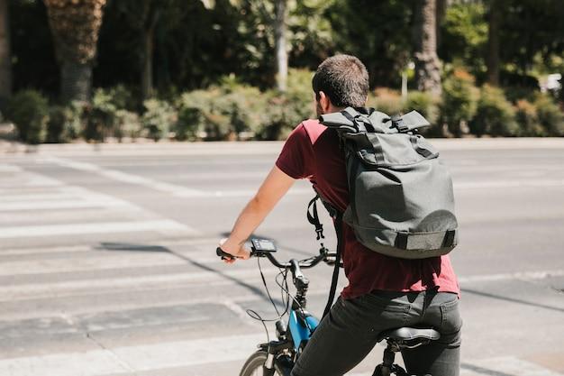 Ciclista di vista posteriore che aspetta al passaggio pedonale