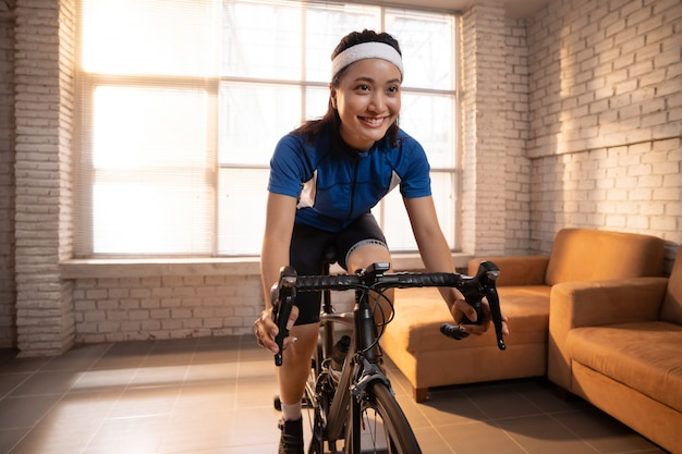 Ciclista donna asiatica. si allena in casa andando in bicicletta con l'allenatore
