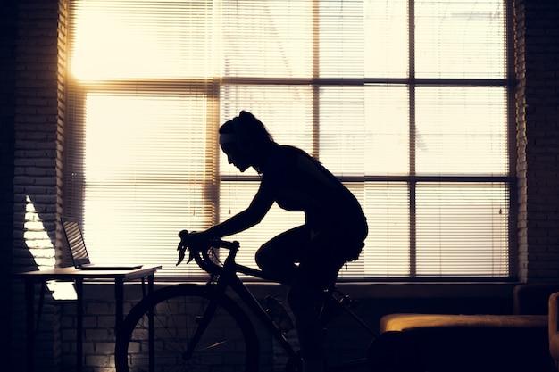 Ciclista donna asiatica. si allena in casa, va in bicicletta sull'allenatore e gioca a giochi di bici online