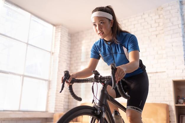 Ciclista donna asiatica. si esercita in casa. in bicicletta sull'allenatore e gioca a giochi di bici online