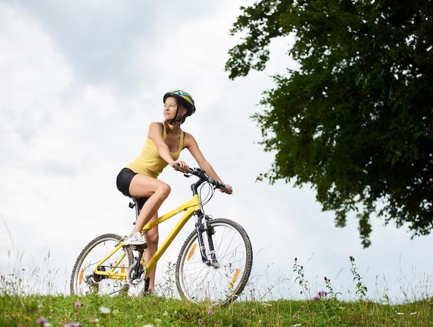 Ciclista felice attraente della donna che guida sulla bicicletta gialla della montagna su una collina erbosa