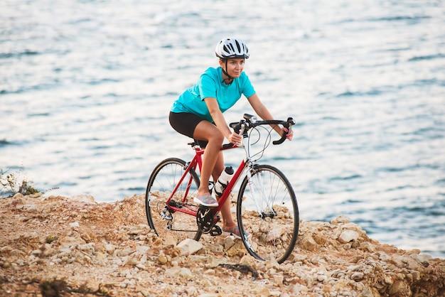 Ciclista femminile che sta su una roccia con la bici e che esamina mare