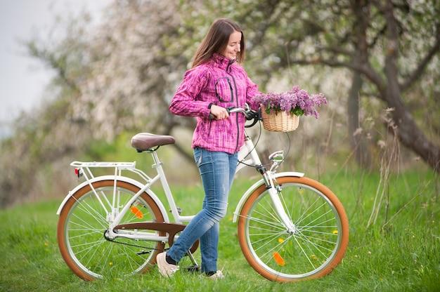 Ciclista femminile con bicicletta bianca dell'annata nel giardino di primavera