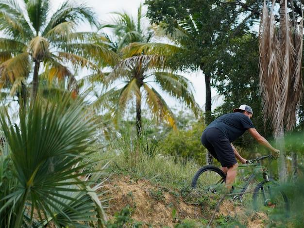 Ciclista in mountain-bike che guida attraverso la giungla. isola tropicale.