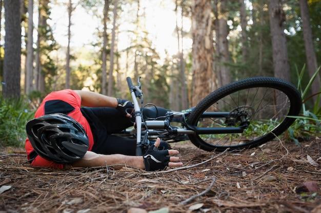 Ciclista in mountain-bike maschio caduto dalla sua bicicletta nella foresta