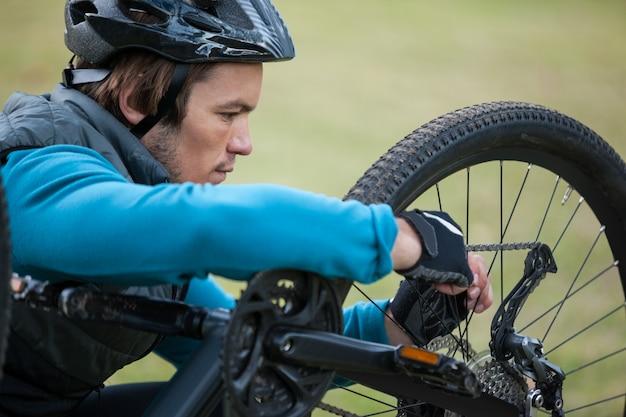Ciclista in mountain-bike maschio che ripara la sua catena della bici