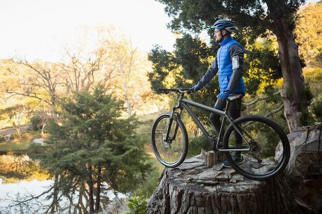 Ciclista in mountain-bike maschio con la bicicletta che esamina natura