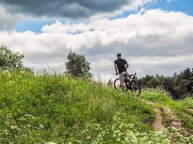 Ciclista in sella alla bici sul bellissimo sentiero di montagna.