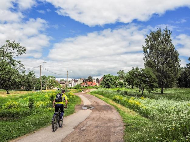 Ciclista in sella alla bici sul bellissimo sentiero rurale.