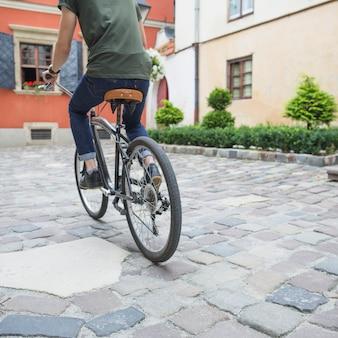 Ciclista in sella alla bicicletta sul marciapiede di pietra
