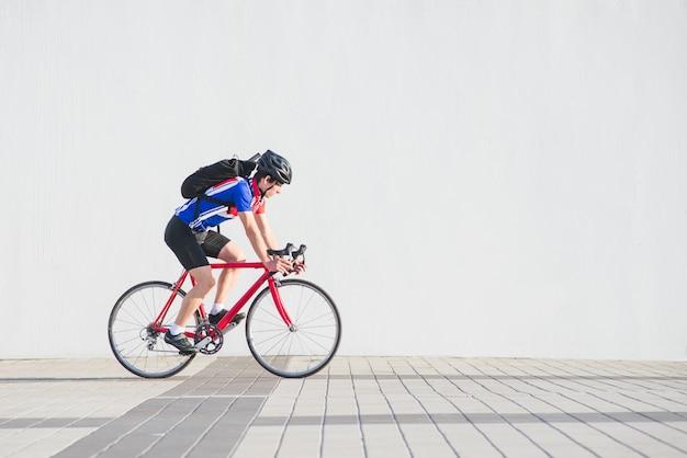 Ciclista in un casco, abiti da ciclismo atletici e uno zaino cavalca su un muro bianco