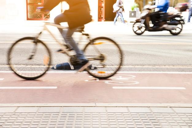 Ciclista irriconoscibile in sella a una bicicletta su una pista ciclabile attraverso la strada cittadina