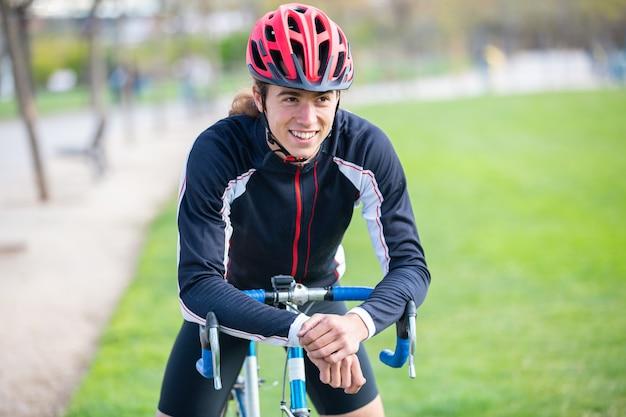 Ciclista maschio adatto sorridente dei giovani in abiti sportivi e casco che si siedono sulla bici in parco e che esaminano macchina fotografica