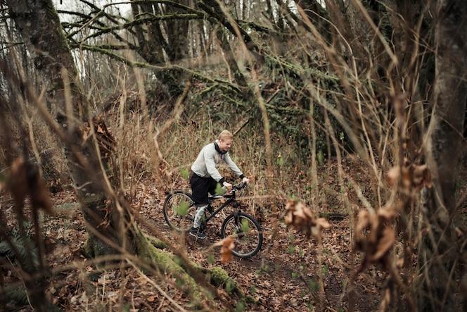 Ciclista maschio che guida nella foresta