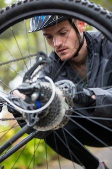 Ciclista maschio che ripara la sua mountain bike