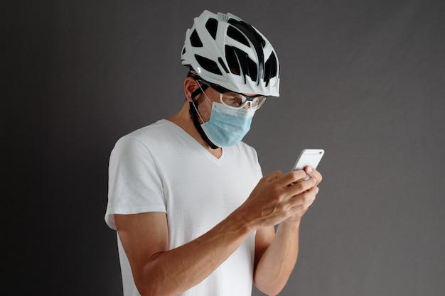 Ciclista maschio in casco bianco e maschera protettiva respiratoria utilizza smartphone.