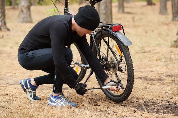 Ciclista mountain bike che ripara la gomma a terra oohis bici nella foresta, giovane maschio in posa all'indietro, ragazzo squating vicino alla sua bici