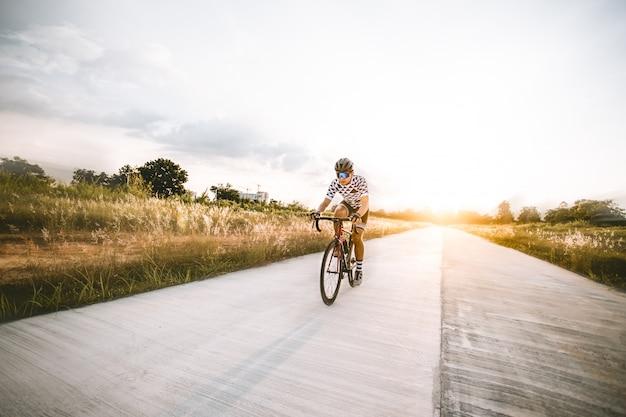 Ciclista uomo asiatico in sella a una bicicletta su una strada aperta verso il tramonto.