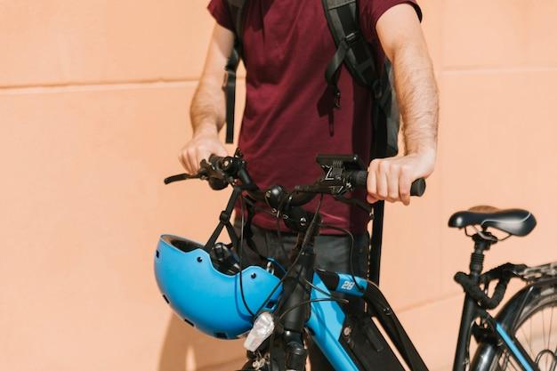 Ciclista urbano che cammina accanto alla e-bike