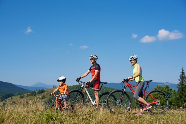 Ciclisti, madre, padre e bambino turistici felici della famiglia che riposano con le biciclette sulla cima della collina erbosa, esaminando distanza, il giorno soleggiato di estate. stile di vita attivo, concetto di viaggio e relazioni