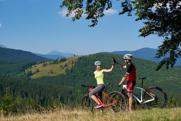 Ciclisti, uomo e donna felici delle coppie con le bici sulla collina erbosa sotto il grande ramo di albero verde, sorridenti e dando il livello cinque il giorno di estate soleggiato. bella vista della catena montuosa sullo sfondo