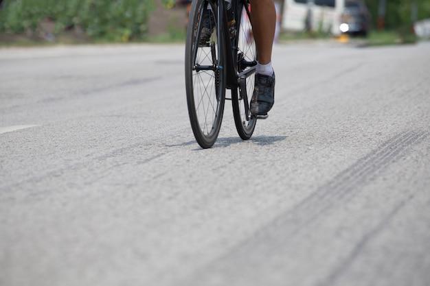 Cicloturismo, guida una bici su strada asfaltata.