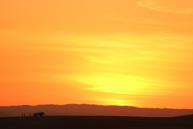 Cielo di aunset sopra la duna di sabbia del deserto di huacachina con la siluetta del carrozzino e dei turisti di duna, perù