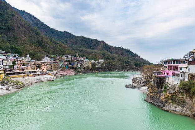 Cielo drammatico a rishikesh, città santa e destinazione del viaggio in india. cielo colorato e nuvole che riflettono sul fiume gange.