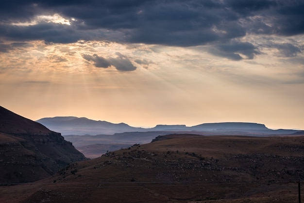 Cielo drammatico, nuvole temporalesche e raggi di sole su vallate, canyon e montagne da tavola dei maestosi.